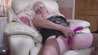 Full-grown busty blonde BBW Cindy S. plays with a dildo surrounding her pussy